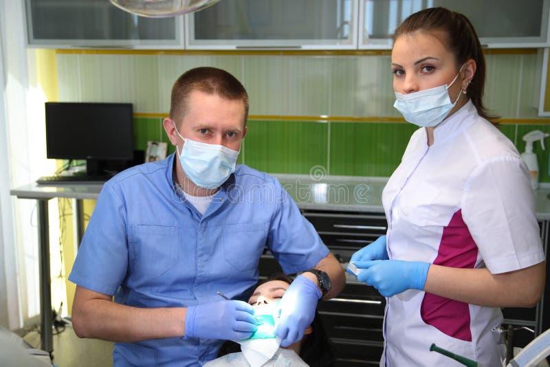 Dentista che tratta i denti del ` una s del paziente con gli strumenti dentari in clinica dentaria odontoiatria fotografie stock libere da diritti
