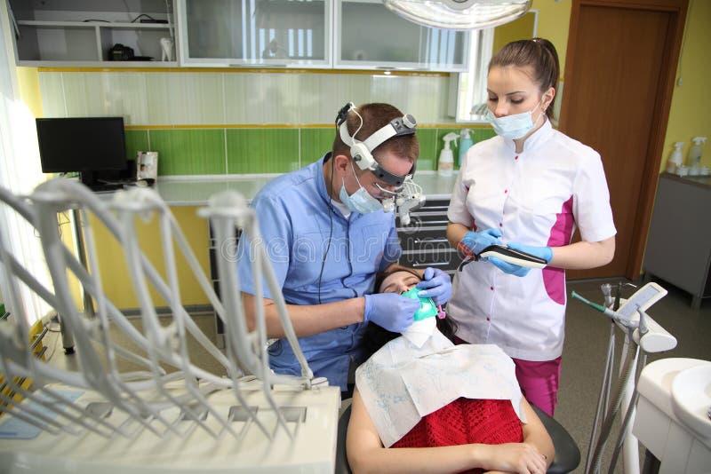 Dentista che tratta i denti del ` una s del paziente con gli strumenti dentari in clinica dentaria odontoiatria immagine stock libera da diritti