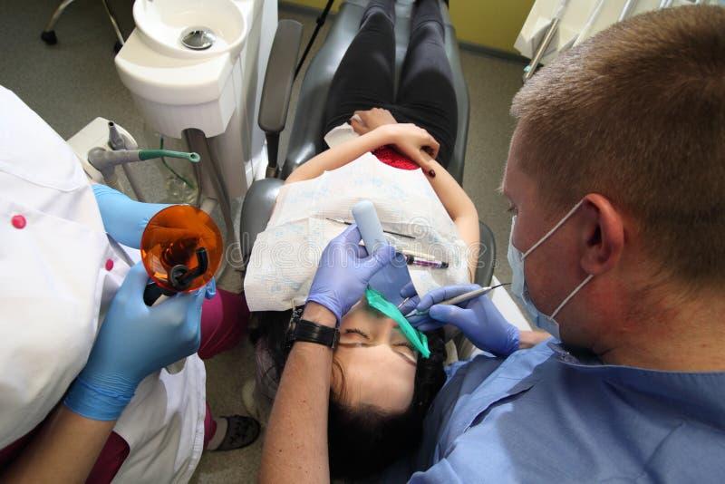 Dentista che tratta i denti del ` una s del paziente con gli strumenti dentari in clinica dentaria odontoiatria immagini stock