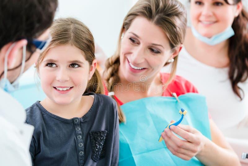 Dentista com mulher gravida e criança na cirurgia fotografia de stock royalty free