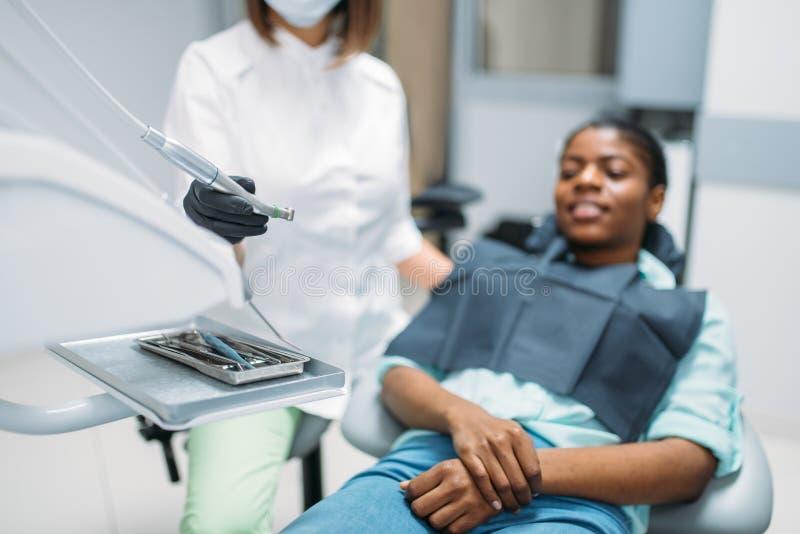 Dentista con il trapano, paziente femminile, clinica dentaria fotografie stock libere da diritti
