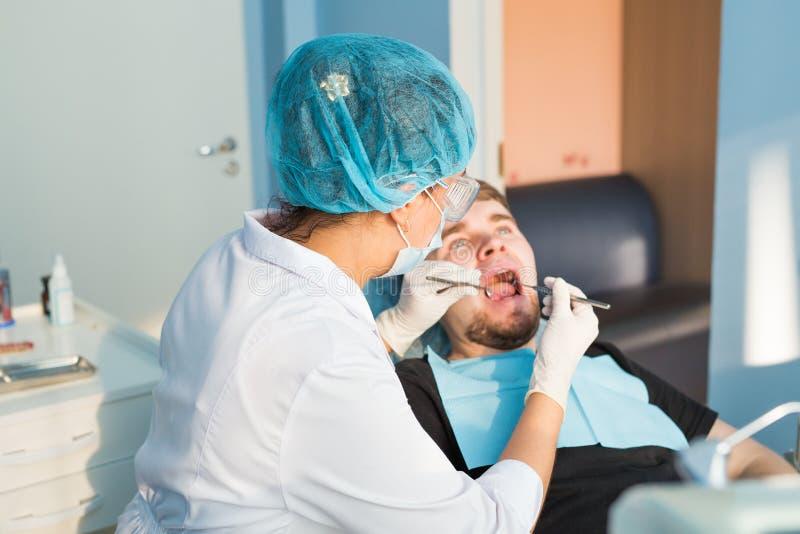 Dentista da mulher no escritório dental médico É cura o paciente fotos de stock