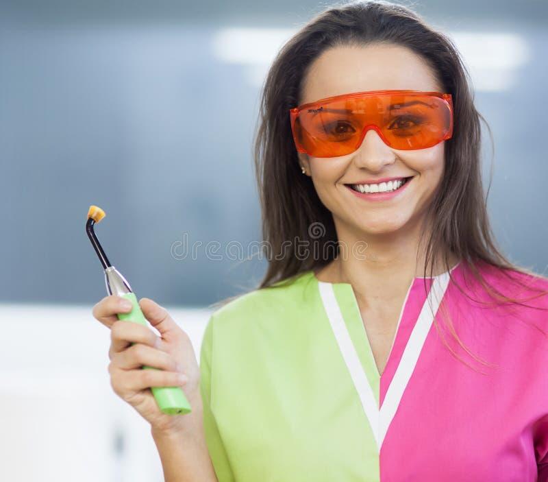 Dentista da mulher que guarda uma lâmpada dental da polimerização imagens de stock