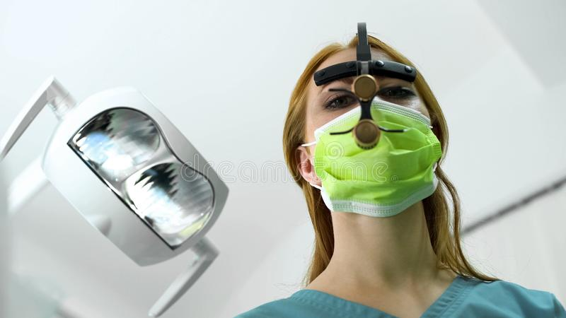 Dentista da senhora que examina a cavidade oral com vidros, stomatology moderno, paciente POV fotos de stock royalty free