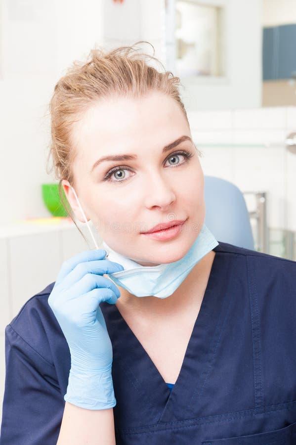 Dentista de la mujer en su uniforme y máscara que llevan de la oficina fotografía de archivo
