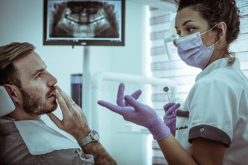 Dentista de la mujer joven que discute con el paciente del hombre fotografía de archivo