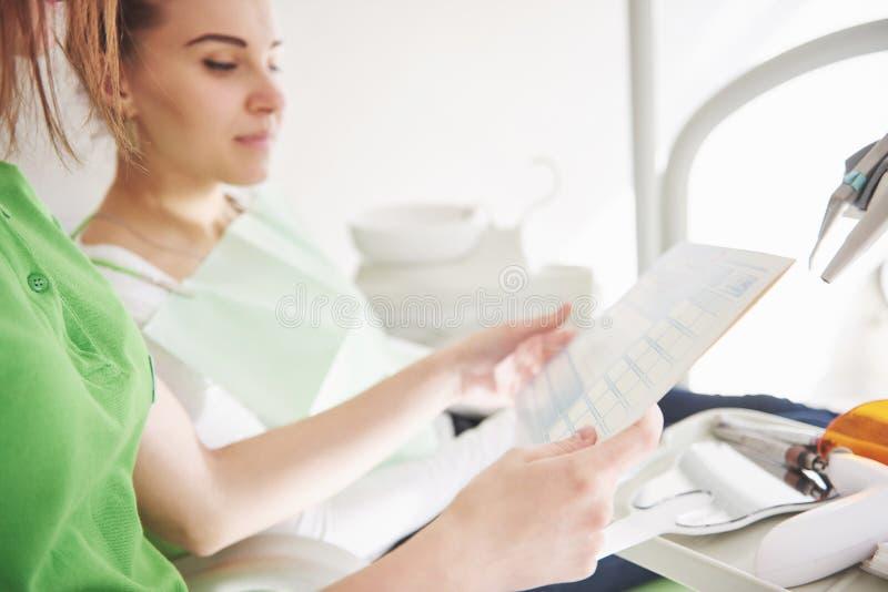 Dentista de sexo femenino en oficina dental que habla con el paciente femenino y que se prepara para el tratamiento fotografía de archivo libre de regalías