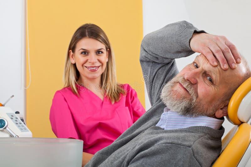 Dentista de sexo femenino joven con el paciente mayor fotos de archivo