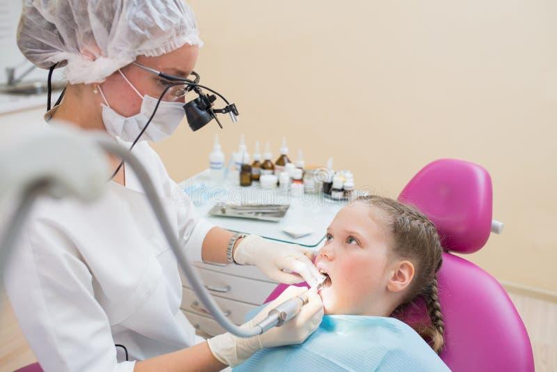Dentista de sexo femenino joven en los prismáticos de la lupa comprobados y que curan los dientes de paciente del niño que se sie fotos de archivo libres de regalías