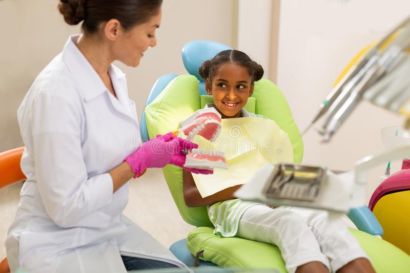 Dentista de sexo femenino oscuro-cabelludo sonriente que usa un modelo dental foto de archivo libre de regalías