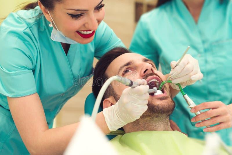Dentista de sexo femenino que examina y que trabaja en paciente masculino joven Oficina del ` s del dentista foto de archivo libre de regalías