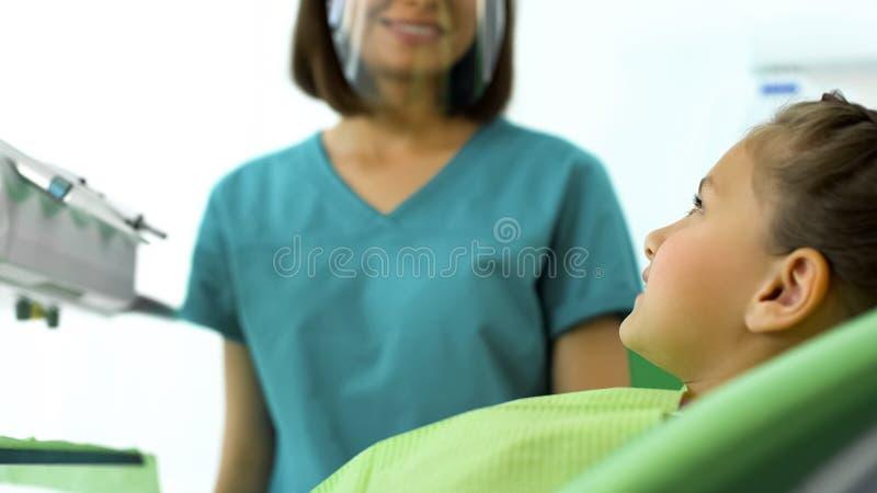 Dentista de sexo femenino que sonríe en el adolescente, dientes de examen del niño del doctor amistoso foto de archivo libre de regalías