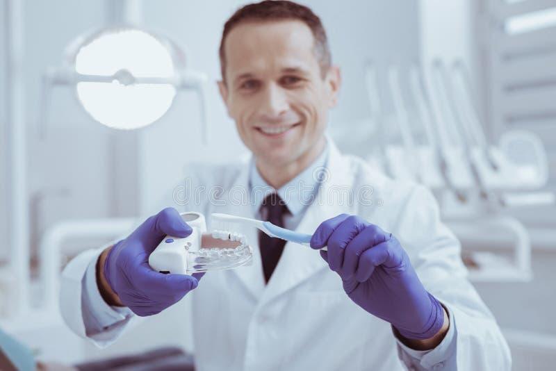 Dentista de sexo masculino alegre que da instrucciones los dientes que limpian en modelo foto de archivo