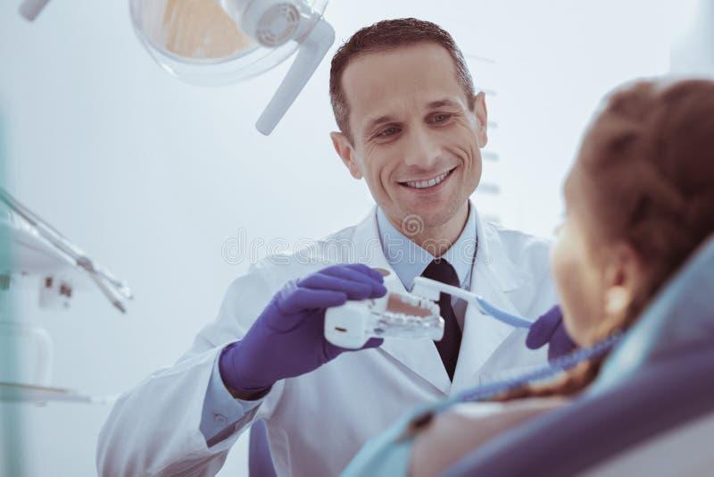 Dentista de sexo masculino alegre que demuestra los dientes que limpian en modelo fotografía de archivo
