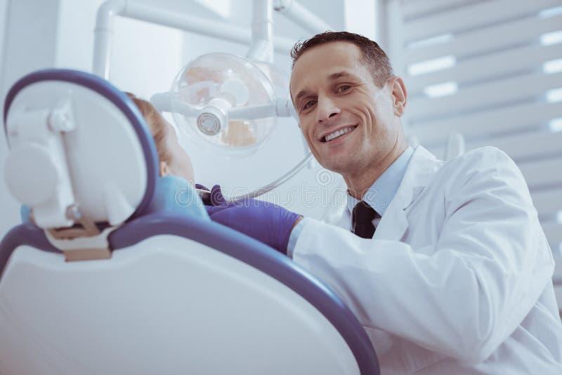 Dentista de sexo masculino alegre que quita decaimiento de los dientes fotografía de archivo libre de regalías