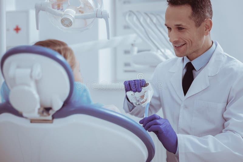 Dentista de sexo masculino confiado que hace el modelo de dentaduras fotografía de archivo libre de regalías