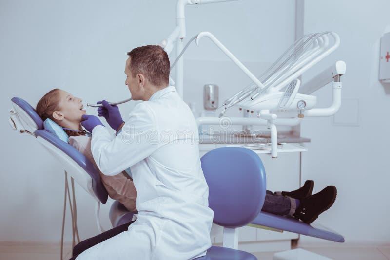 Dentista de sexo masculino experto que quita los dientes imágenes de archivo libres de regalías
