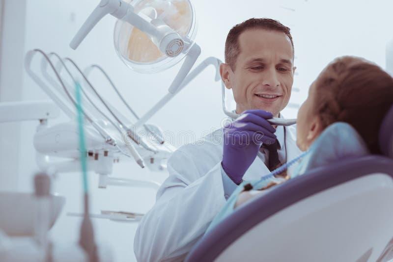 Dentista de sexo masculino experto que ve la cavidad bucal fotografía de archivo