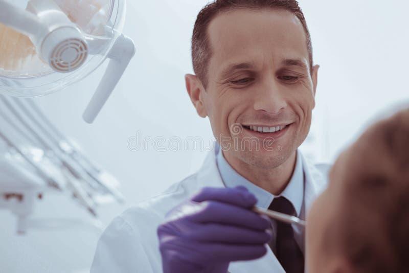 Dentista de sexo masculino positivo que examina la cavidad bucal imágenes de archivo libres de regalías