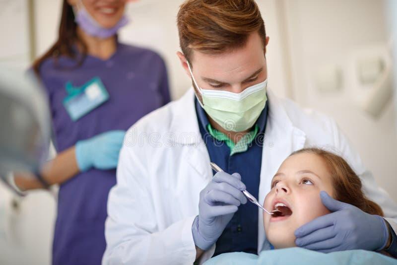 Dentista de sexo masculino que mira con los dientes dentales del ` s del niño del espejo foto de archivo