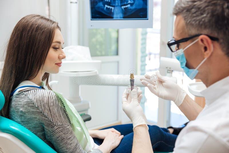 Dentista de sexo masculino que muestra a su paciente femenino un implante dental foto de archivo libre de regalías