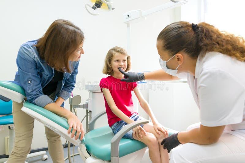 Dentista de visita da mãe e da filha pequena em clínicas dentais O Orthodontist põe sobre, corrige a placa dental na criança foto de stock royalty free