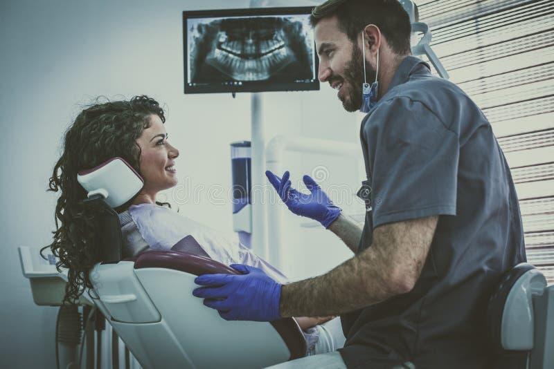 Dentista dell'uomo che ha paziente di spirito di discussione fotografie stock libere da diritti