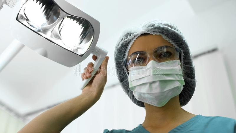 Dentista di signora che regola le luci operatory, preparazione per chirurgia, paziente POV immagine stock libera da diritti