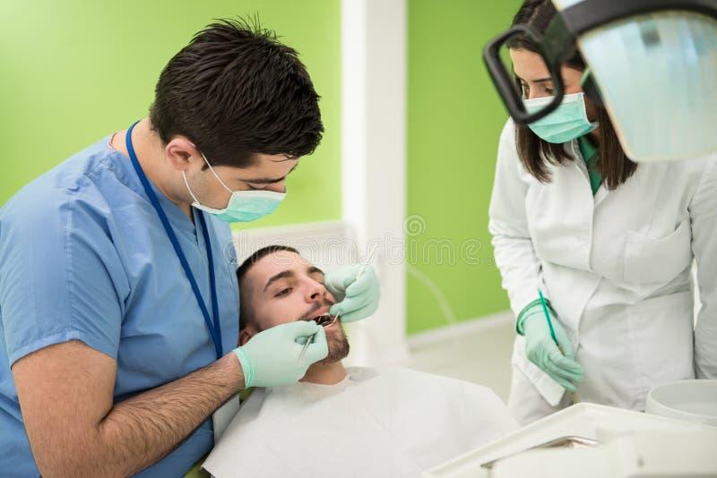 Dentista Doing un tratamiento dental en paciente fotografía de archivo