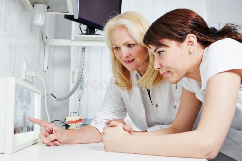 Dentista e assistand dental que olham a imagem do raio X foto de stock