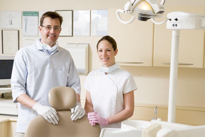 Dentista e assistente no quarto do exame fotos de stock