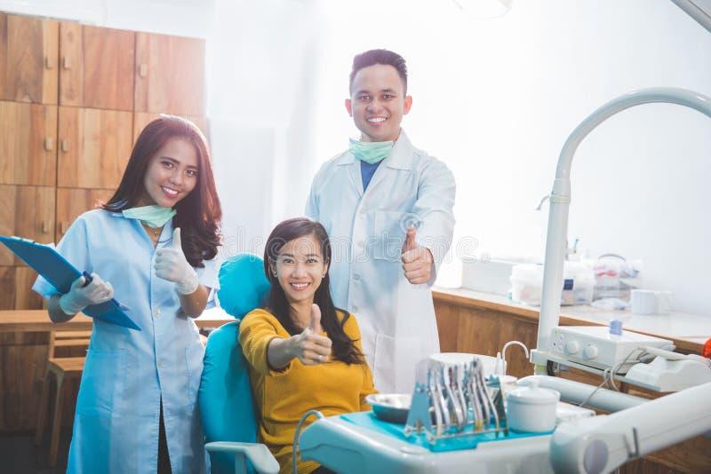 Dentista e paciente que dão os polegares acima no escritório do dentista imagens de stock