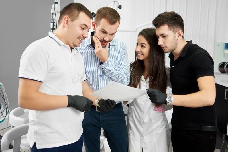 Dentista e suas instruções assistentes dos pacientes da mostra para cuidados dentários foto de stock royalty free