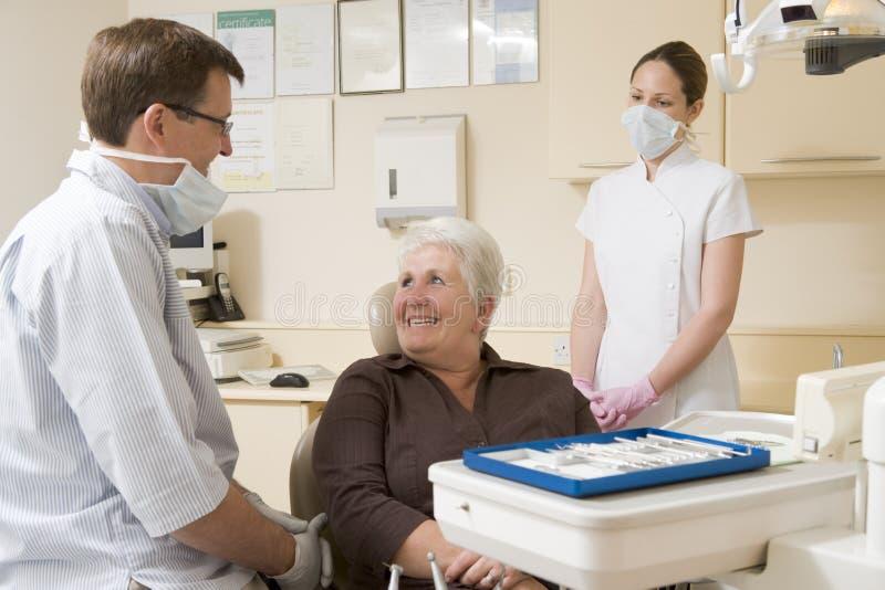 Dentista ed assistente nella stanza dell'esame con fotografia stock