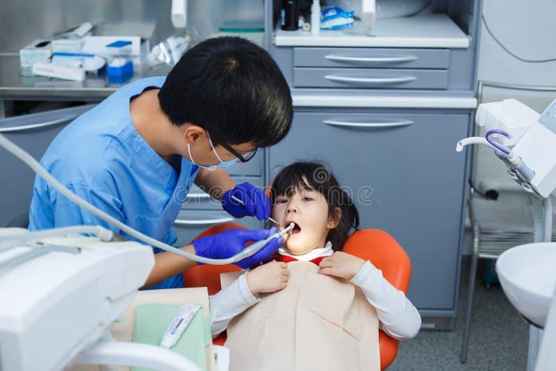 Dentista en el trabajo Dientes del ` s de la niña de la limpieza del doctor pediátrico imagen de archivo libre de regalías