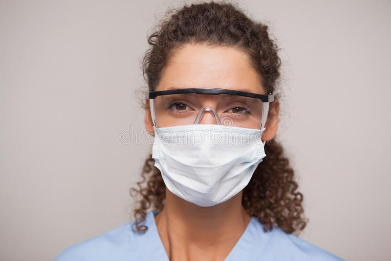 Dentista en máscara quirúrgica y los vidrios protectores que miran la cámara fotografía de archivo