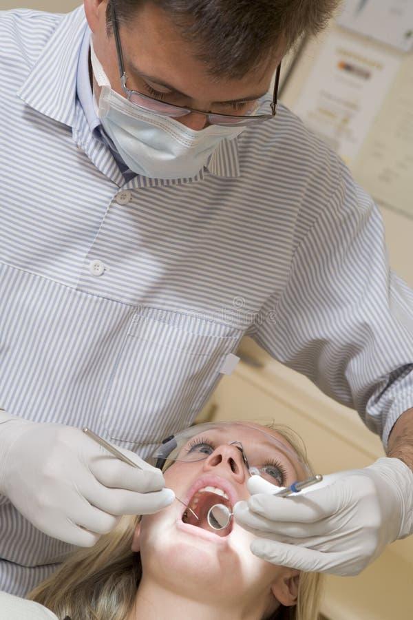 Dentista en sitio del examen con la mujer imagen de archivo