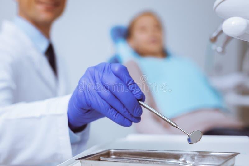 Dentista encantado que toma el dispositivo necesario imagen de archivo