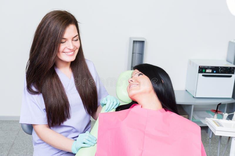 Dentista fêmea amigável que mostra o cuidado para o paciente novo imagem de stock royalty free