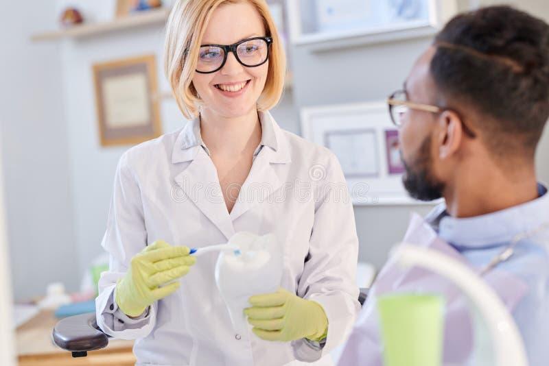 Dentista fêmea de sorriso que guarda a escova de dentes foto de stock royalty free