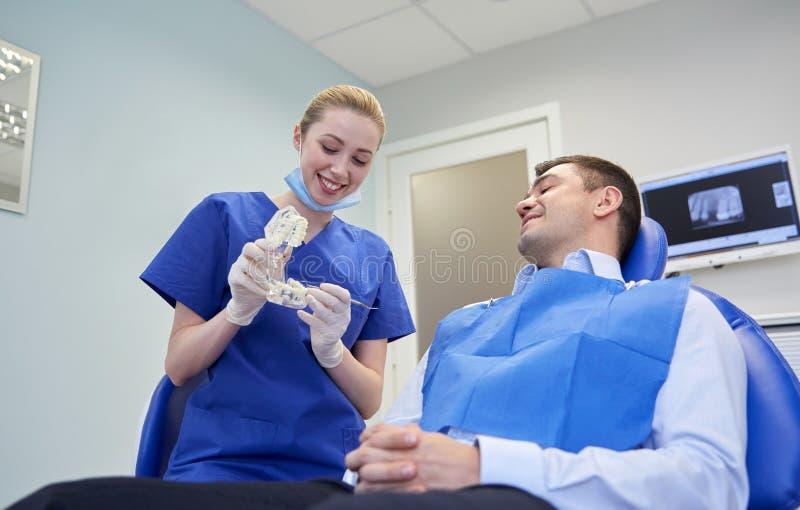 Dentista feliz que muestra la disposición del mandíbula al paciente masculino fotografía de archivo