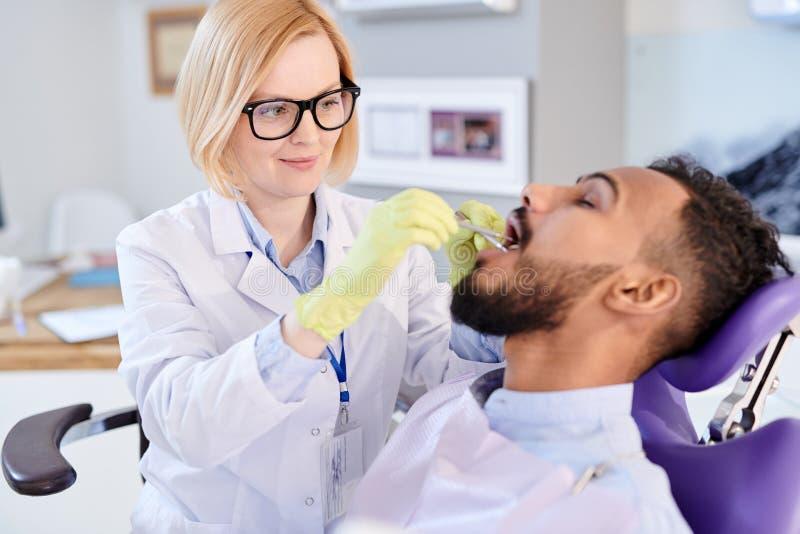 Dentista femminile biondo Working con il paziente immagine stock