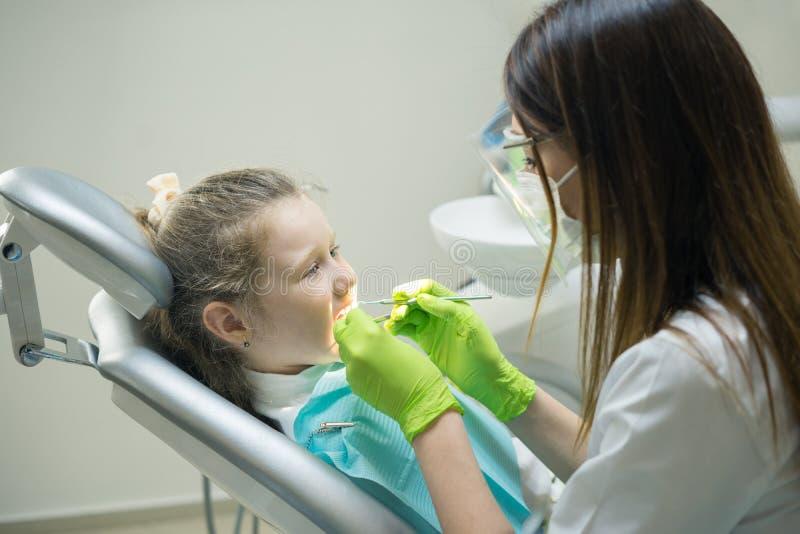 Dentista femminile che controlla il paziente della bambina immagine stock libera da diritti