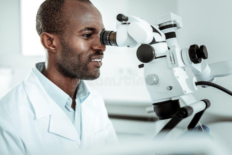 Dentista hermoso en el uniforme blanco especial que mira en cavidad bucal foto de archivo libre de regalías
