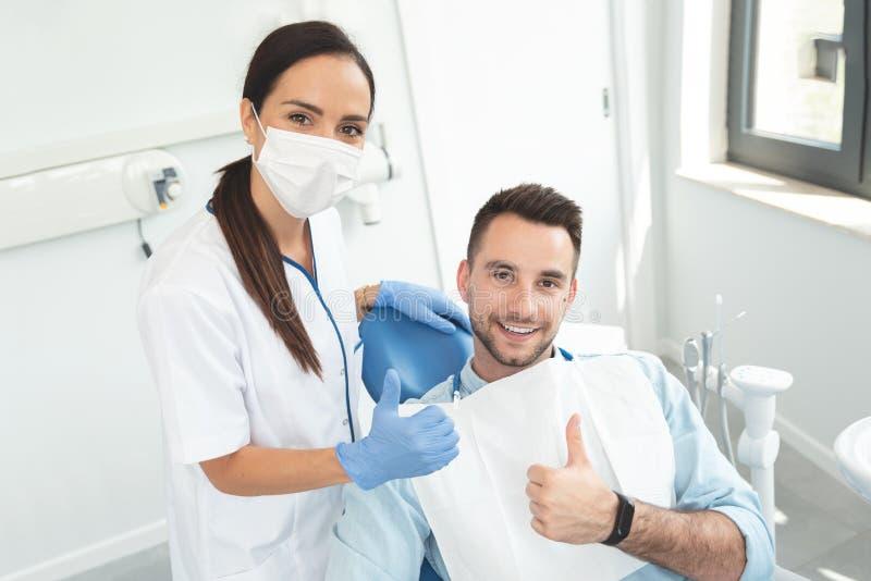 Dentista joven del doctor y pulgar que muestra paciente para arriba imagen de archivo