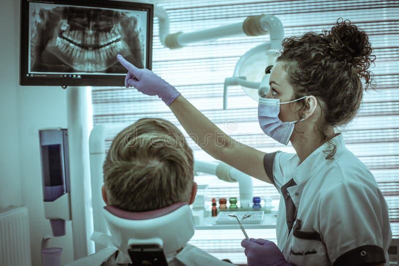 Dentista joven que examina la radiografía médica con el paciente foto de archivo libre de regalías