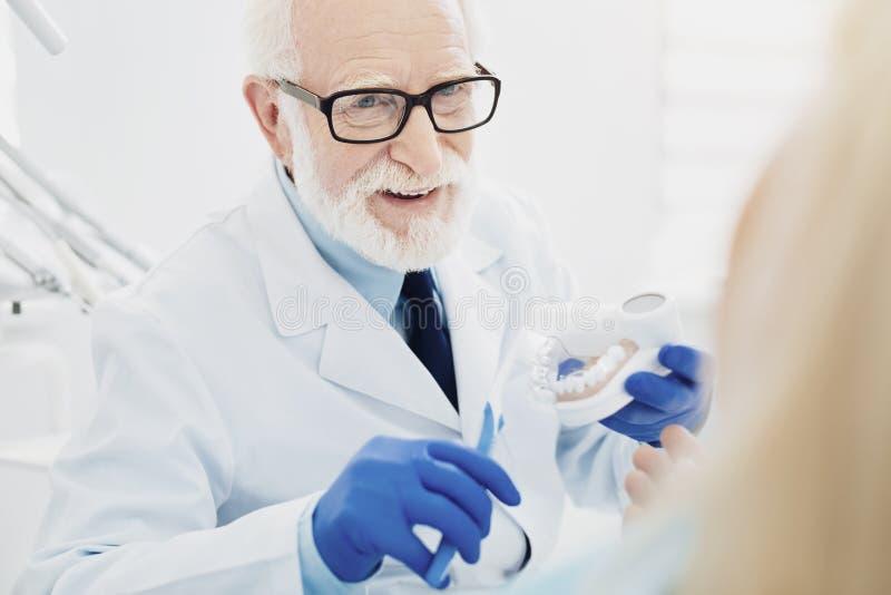 Dentista maschio allegro che dimostra pulizia dei denti fotografia stock libera da diritti