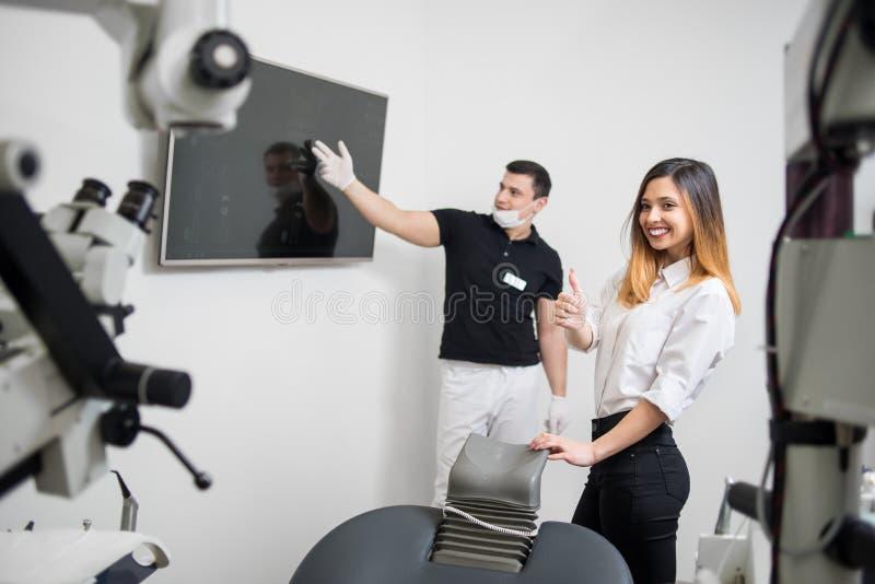Dentista maschio che mostra immagine dentaria dei raggi x sul monitor del computer in una clinica dentaria odontoiatria immagini stock