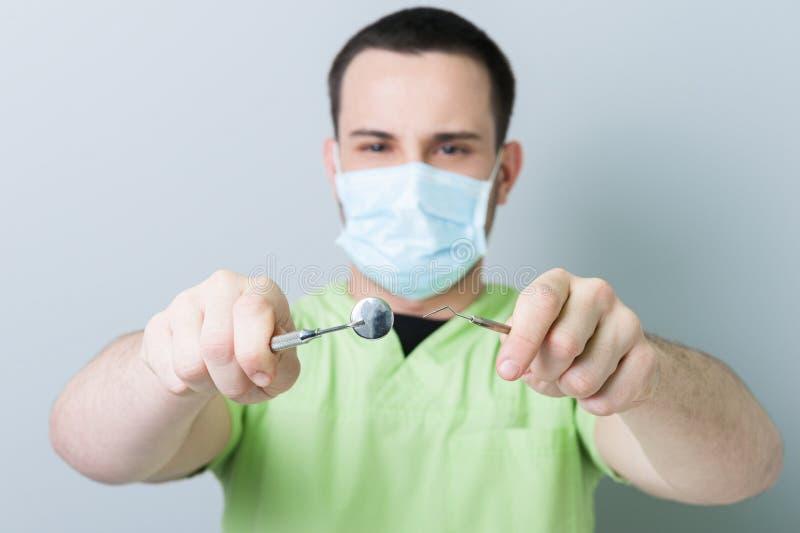 Dentista maschio che posa la smerigliatrice e lo specchio della tenuta immagine stock