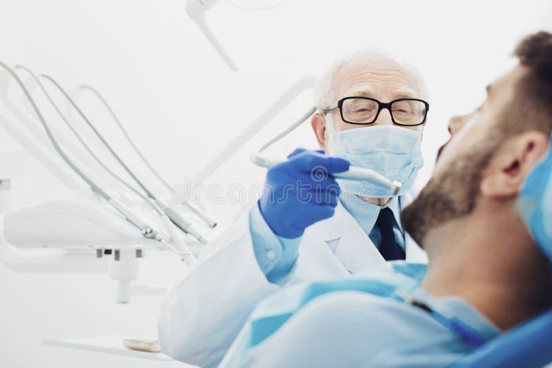 Dentista maschio con esperienza che sostituisce dente fotografie stock
